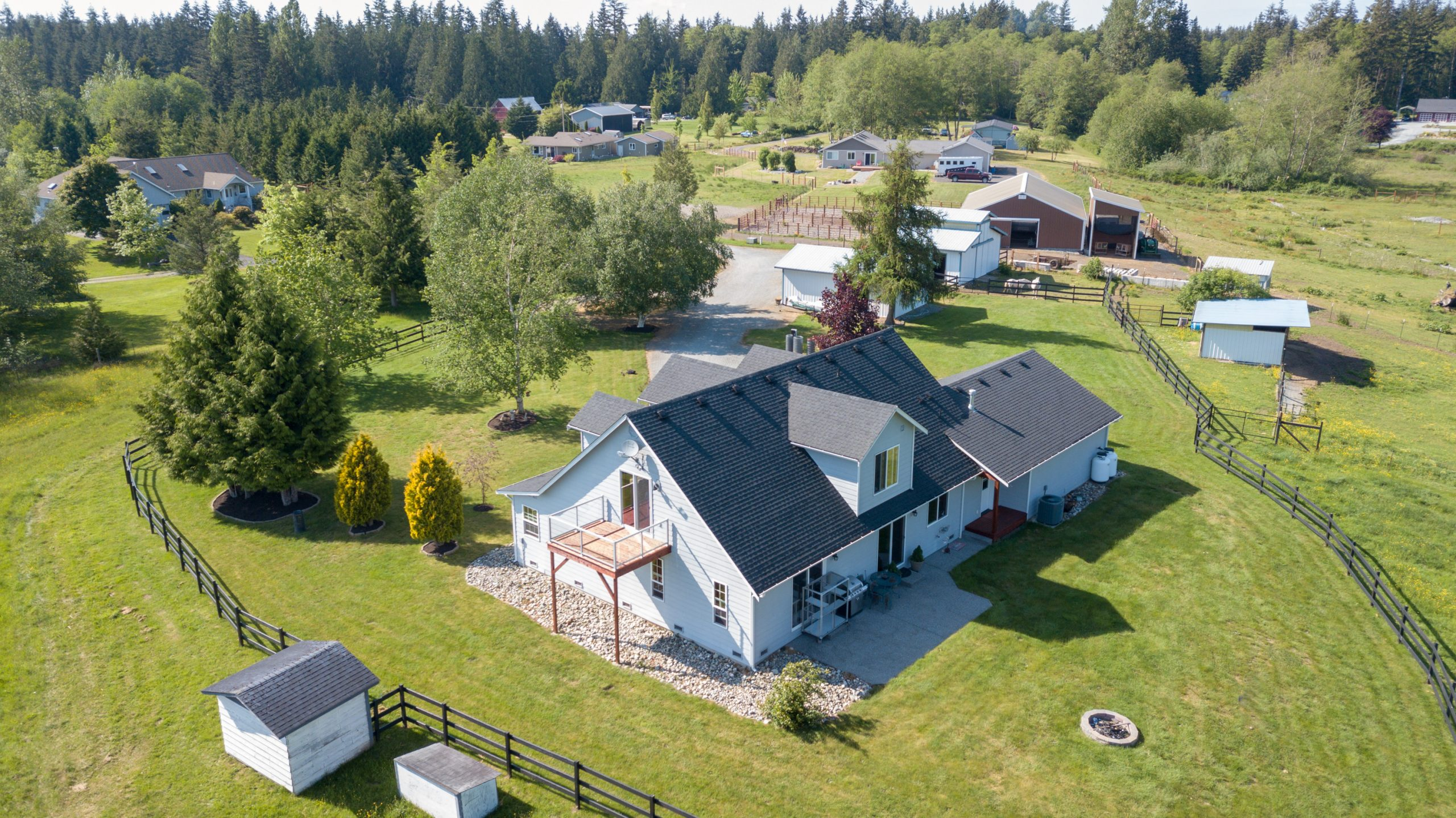 Drone photo of single farm house with grey roof and large green grass yard.